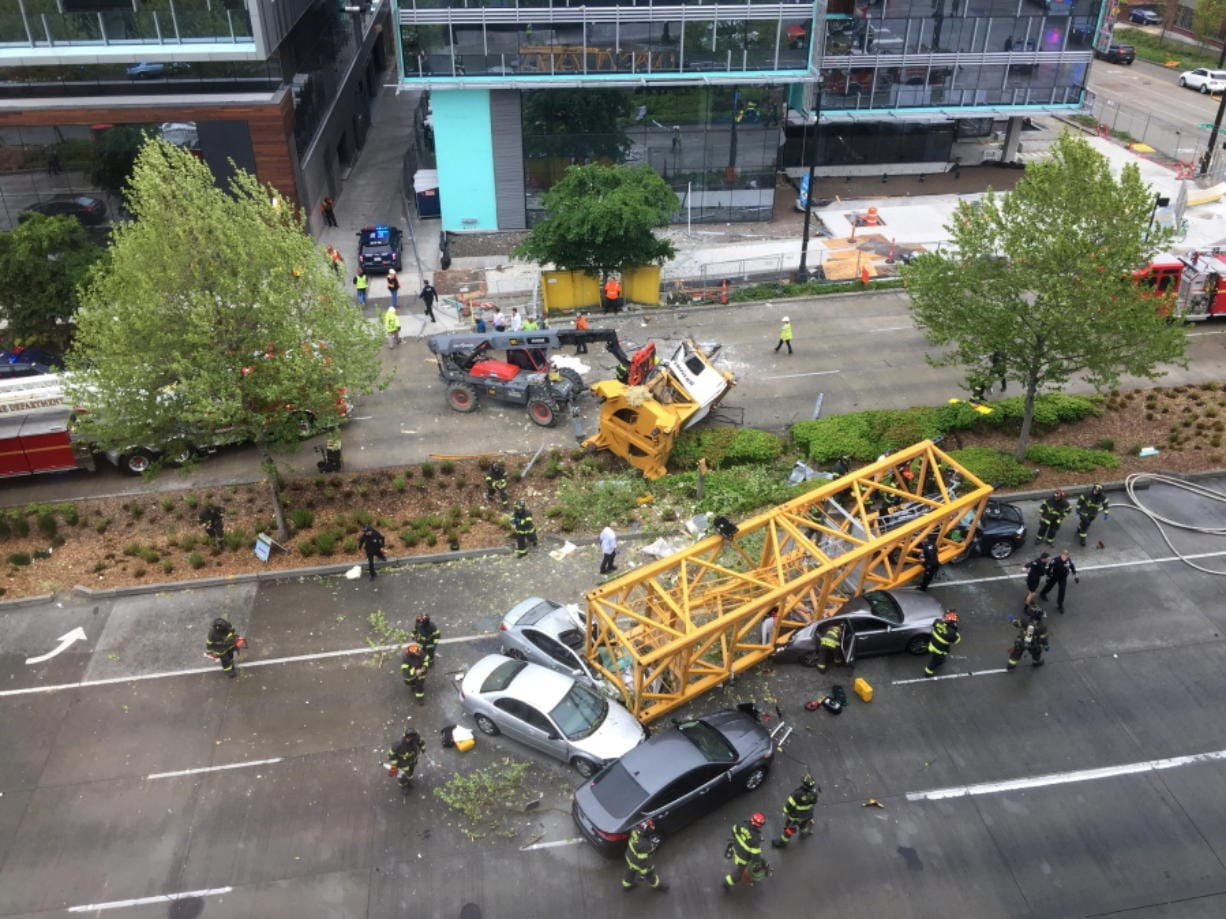 FILE - In this April 27, 2019, file photo, fire and police crew members work to clear the scene where a construction crane fell from a building on Google's new Seattle campus, crashing down onto one of the city's busiest streets and killing four people. Washington state's Department of Labor and Industries released the results of its investigation into the collapse Thursday, Oct. 17, 2019. It found, as experts have long suspected, that the crane toppled because workers who were disassembling it had prematurely removed pins securing the sections of the crane's mast.