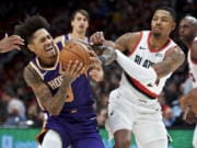 Phoenix Suns forward Kelly Oubre Jr., left, drives to the basket past Portland Trail Blazers guard Kent Bazemore during the second half of a preseason NBA basketball game in Portland, Ore., Saturday, Oct. 12, 2019.
