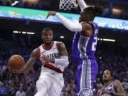 Portland Trail Blazers guard Damian Lillard, left, passes against Sacramento Kings forward Richaun Holmes during the first quarter of an NBA basketball game in Sacramento, Calif., Friday, Oct. 25, 2019.