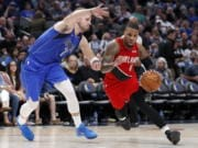 Dallas Mavericks guard Luka Doncic, left, defends agains a drive to the basket by Portland Trail Blazers' Damian Lillard (0) in the second half of an NBA basketball game in Dallas, Sunday, Oct. 27, 2019.