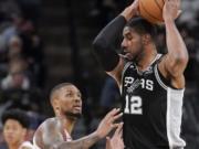 San Antonio Spurs' LaMarcus Aldridge (12) drives against Portland Trail Blazers' Damian Lillard during the second half of an NBA basketball game, Monday, Oct. 28, 2019, in San Antonio. San Antonio won 113-110.