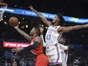Portland Trail Blazers guard Damian Lillard, left, shoots next to Oklahoma City Thunder guard Terrance Ferguson, right, during the second half of an NBA basketball game Wednesday, Oct. 30, 2019, in Oklahoma City.