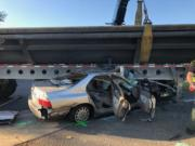 A driver is in critical condition after being pinned under a tractor-trailer Wednesday afternoon in east Vancouver.