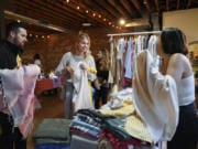 Seth Alcott, left, and his wife, Noelle Alcott, of Vancouver decide on a Turkish towel with the help of Elif Sari Genc, right, the owner of Hands on Hips, a Turkish towels and textiles shop, at the Night Market Vancouver last year.