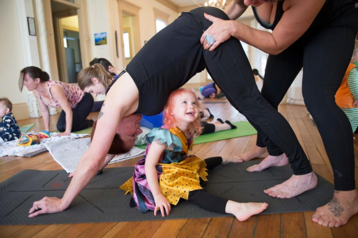 Saffron Smith, 2, looks up while yoga teacher Daniele Strawmyre helps her mother, Jennifer Smith, with a downward dog pose during a Ready Set Grow yoga class at the Slocum House in Esther Short Park on Saturday, October 26, 2019. Ready Set Grow is a yoga studio based in Portland and Vancouver.