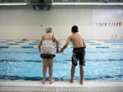Mollie Hands, left, and Gabe Pizzo, 14, stand poised to jump into the pool on the count of three at the Washington State School for the Blind. While Hands made the plunge, Gabe remained at the edge of the pool giggling at his trick. When Hands broke the surface laughing, Gabe jumped in to join her.