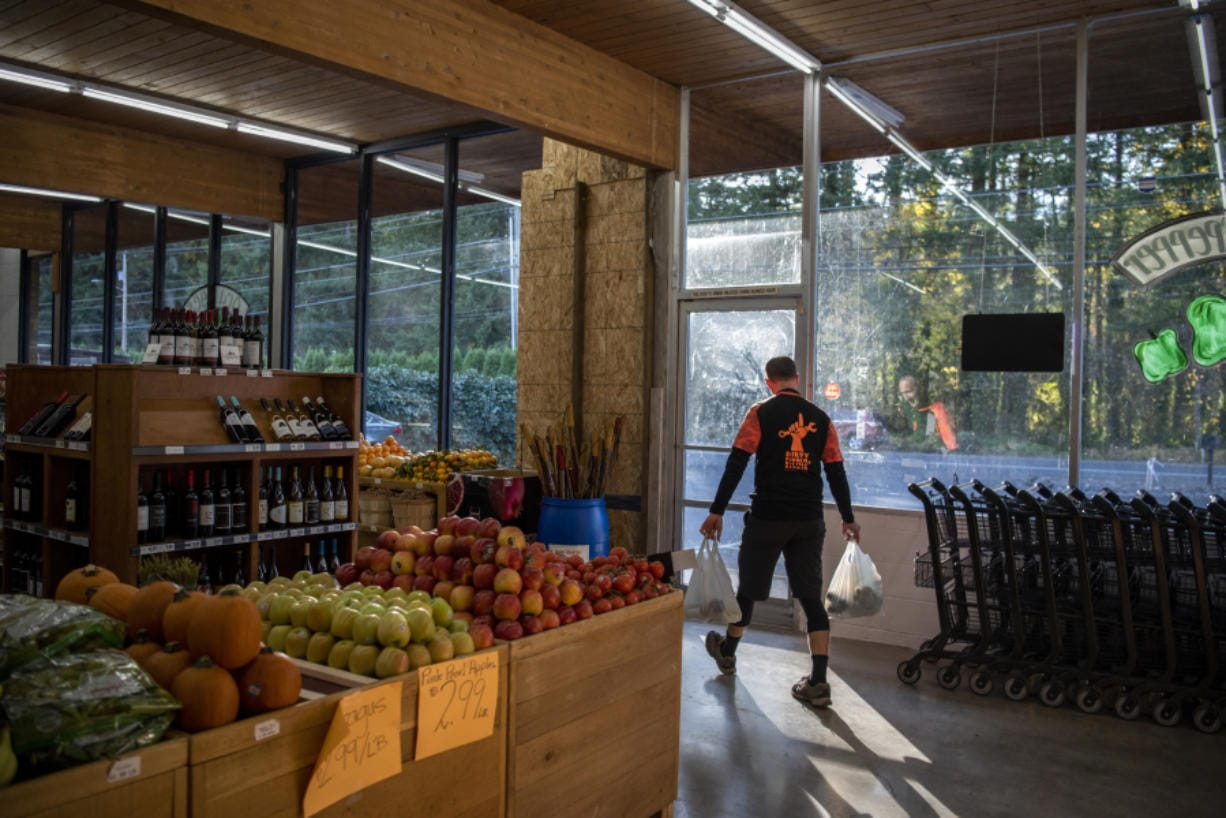 """Adam Nelson of Camas heads out the door at Camas Produce, where a driver drove through the front of the store nearly 10 months ago. """"It's nice to have it back,"""" he said."""