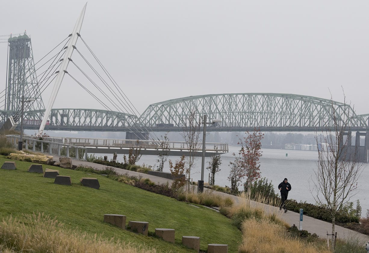 """Battle Ground resident James Fields takes the fog in stride while running near the Grant Street Pier as stagnant air causes the fall air to linger Monday morning, Nov. 4, 2019. Fields, who works in Vancouver, said he was been enjoying the sport since junior high and the cool, seasonal temperatures were a bonus for joggers. """"This is a beautiful time to run,"""" he said."""