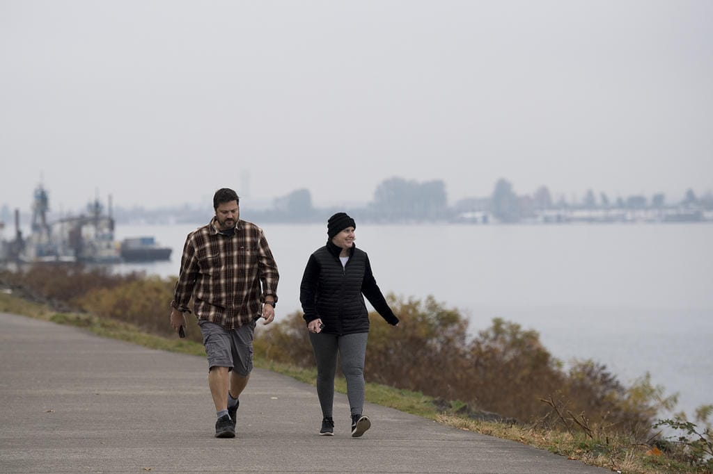 """Vancouver residents Justin and Kelly Venetucci take in a foggy view of the Columbia River while enjoying a brisk, fall walk together Monday morning, Nov. 4, 2019. The couple said they try to walk together almost everyday although they wouldn't mind if blue skies made an appearance again. """"I like the sunny fall,"""" Kelly Venetucci said."""