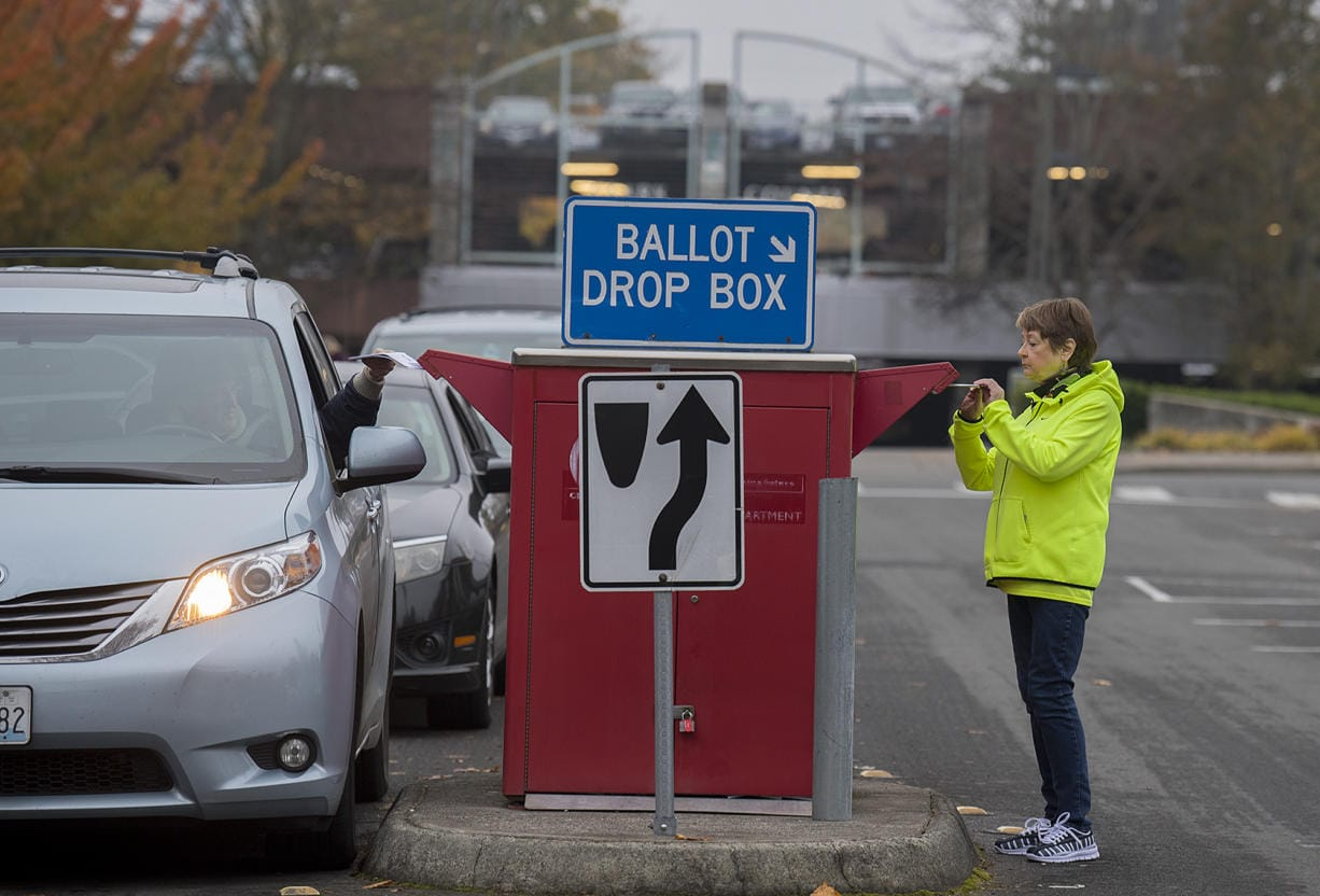 Jan Trygg of Vancouver drops off her ballot on foot at the downtown drop-off box on Tuesday morning.
