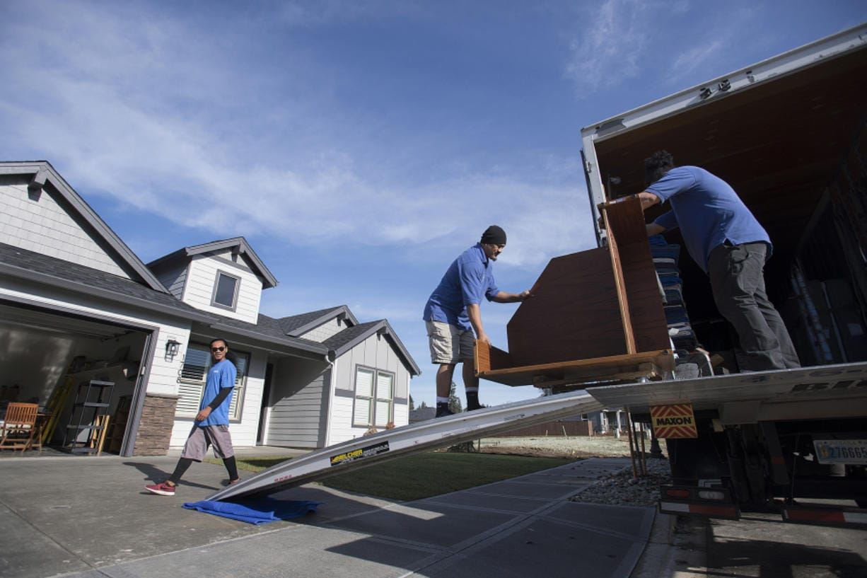 Ivan Heather, from left, of Big Al's Specialty Movers joins colleagues Leonard Malauulu and George Aiono as they transport furniture into a new home in southeast Battle Ground's Cedars Village on Monday morning.