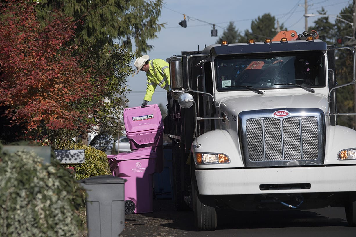 Ben Dynes, a driver with Waste Connections, drops off a pink recycle bin in honor of breast cancer awareness at a home along Devine Road on Wednesday morning, Nov. 6, 2019. (Amanda Cowan/The Columbian)