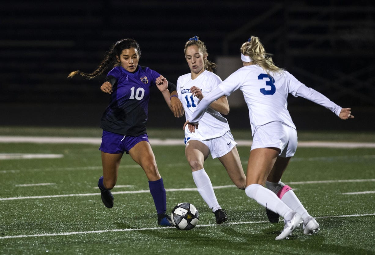 Columbia RiverÕs Yaneisy Rodriguez (10) fights for the ball against RidgefieldÕs Claire Jones (11) during the 2A district championship at Columbia River High School in Vancouver on Nov. 7, 2019. Ridgefield won 2-1.  (Alisha Jucevic/The Columbian)