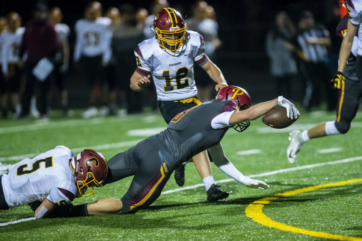 Prairie's Jamien Farrell reaches for extra yards while being brought down by a Capital defender during a game at Battle Ground District Stadium on Friday night, Nov. 8, 2019.