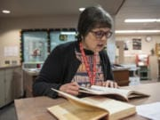 High school librarian Kate Burton flips through the 1943 Alki yearbook at Fort Vancouver High School, looking for a photo of Francis Elaine Bailey.