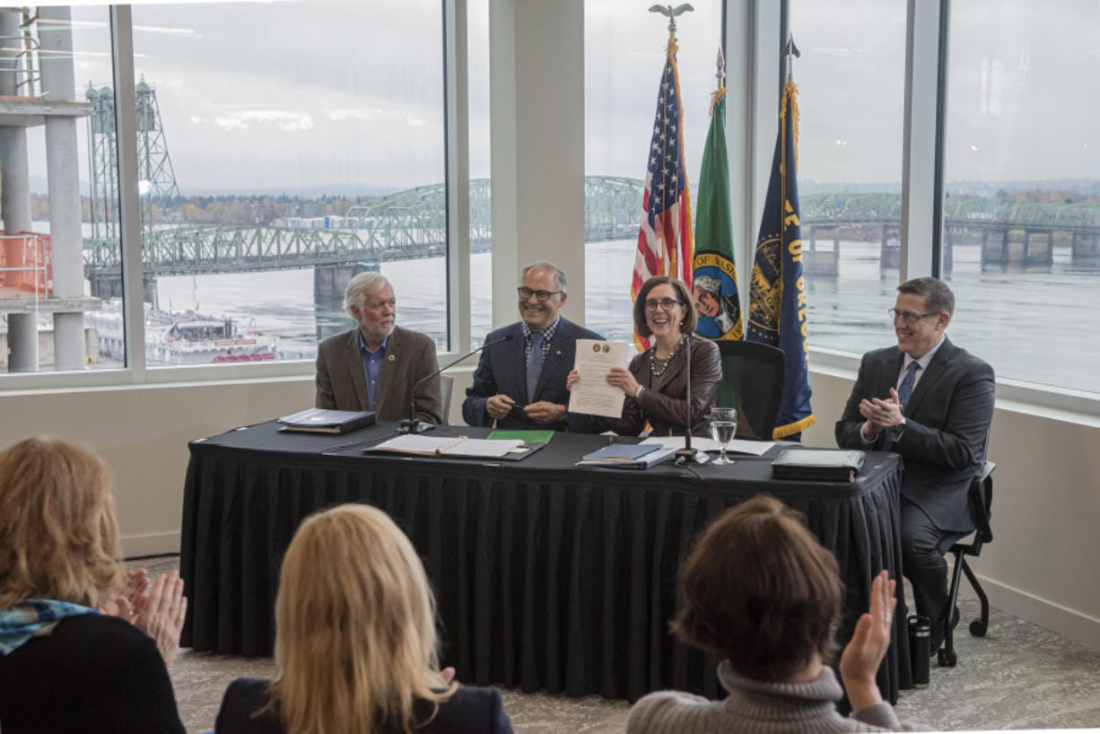 Roger Millar, Washington state secretary of transportation, from left, Washington Gov. Jay Inslee, Oregon Gov. Kate Brown and Kris Strickler, director of the Oregon Department of Transportation, applaud the signing of a memorandum of intent to replace the Interstate 5 bridge at the Murdock Charitable Trust on Monday morning, Nov. 18, 2019.