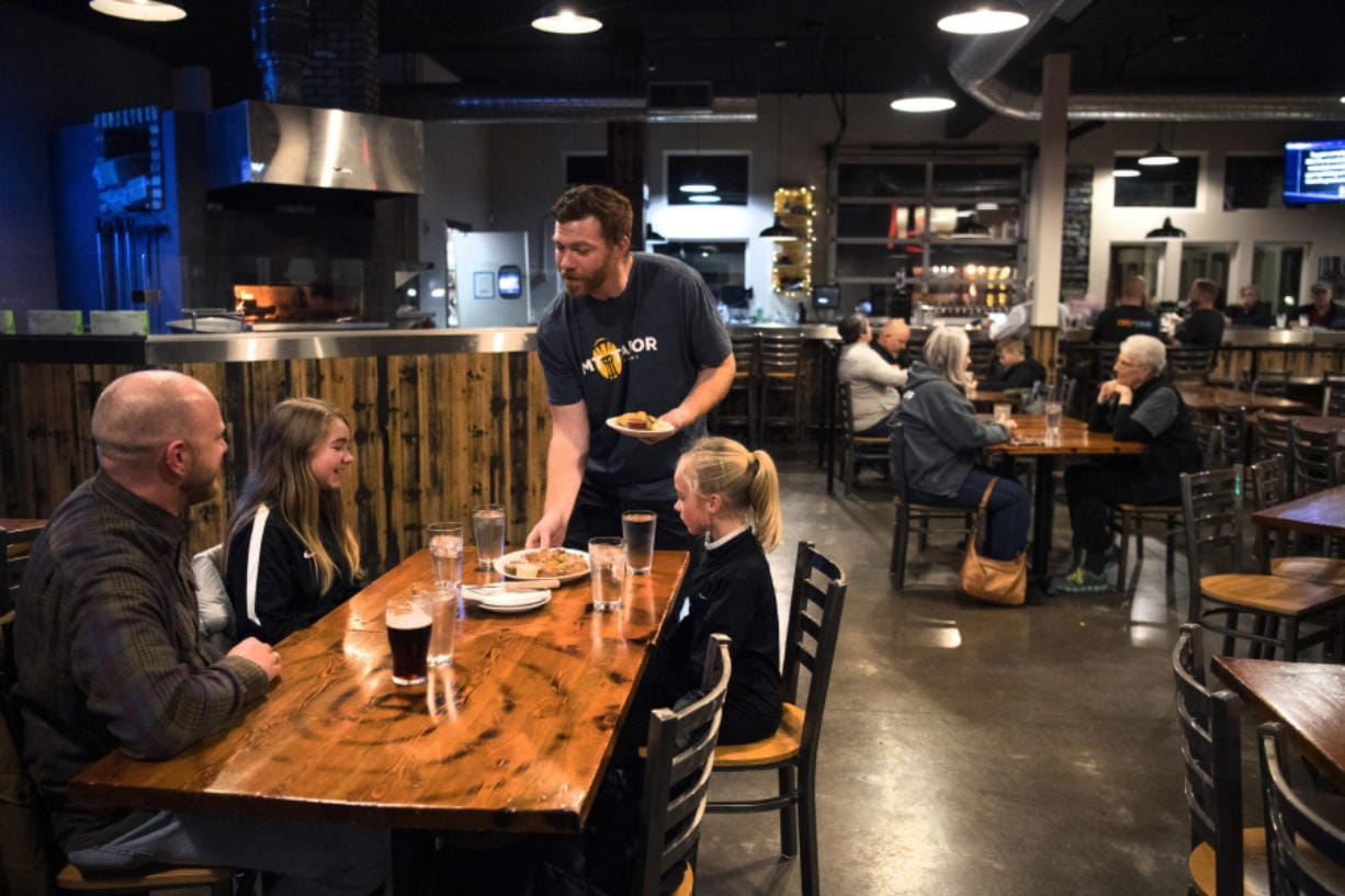"""Bartender and server Garrett Lawler, center, serves customers at Mt. Tabor Brewing in Felida on Tuesday evening. Lawler said he's looking forward to the increase in minimum wage. """"It's absolutely fantastic,"""" he said. Top: Lawler pours beer at Mt. Tabor Brewing."""