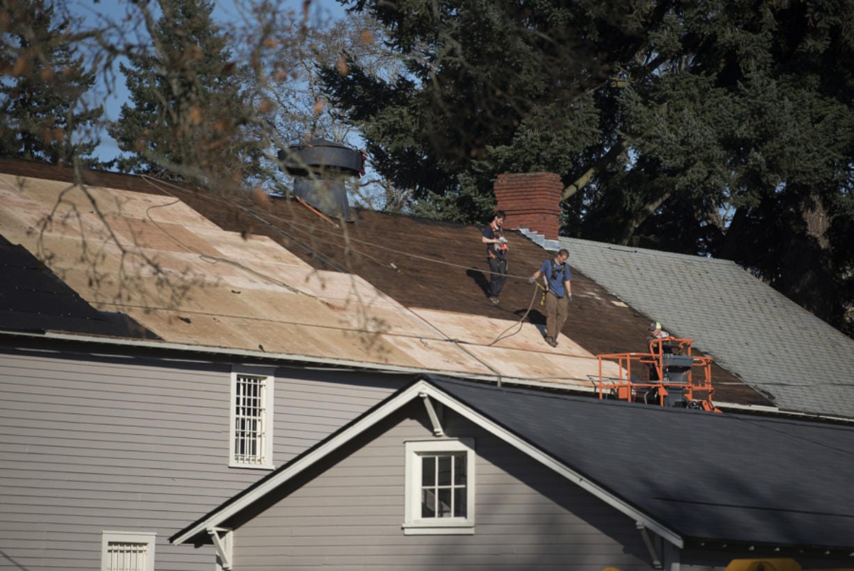 Construction crews help install a new roof at the Quartermaster Storehouse while preserving the original historic fabric at Fort Vancouver National Site on Nov. 21. The old storehouse was one of 16 historic buildings at the site to receive a new roof.