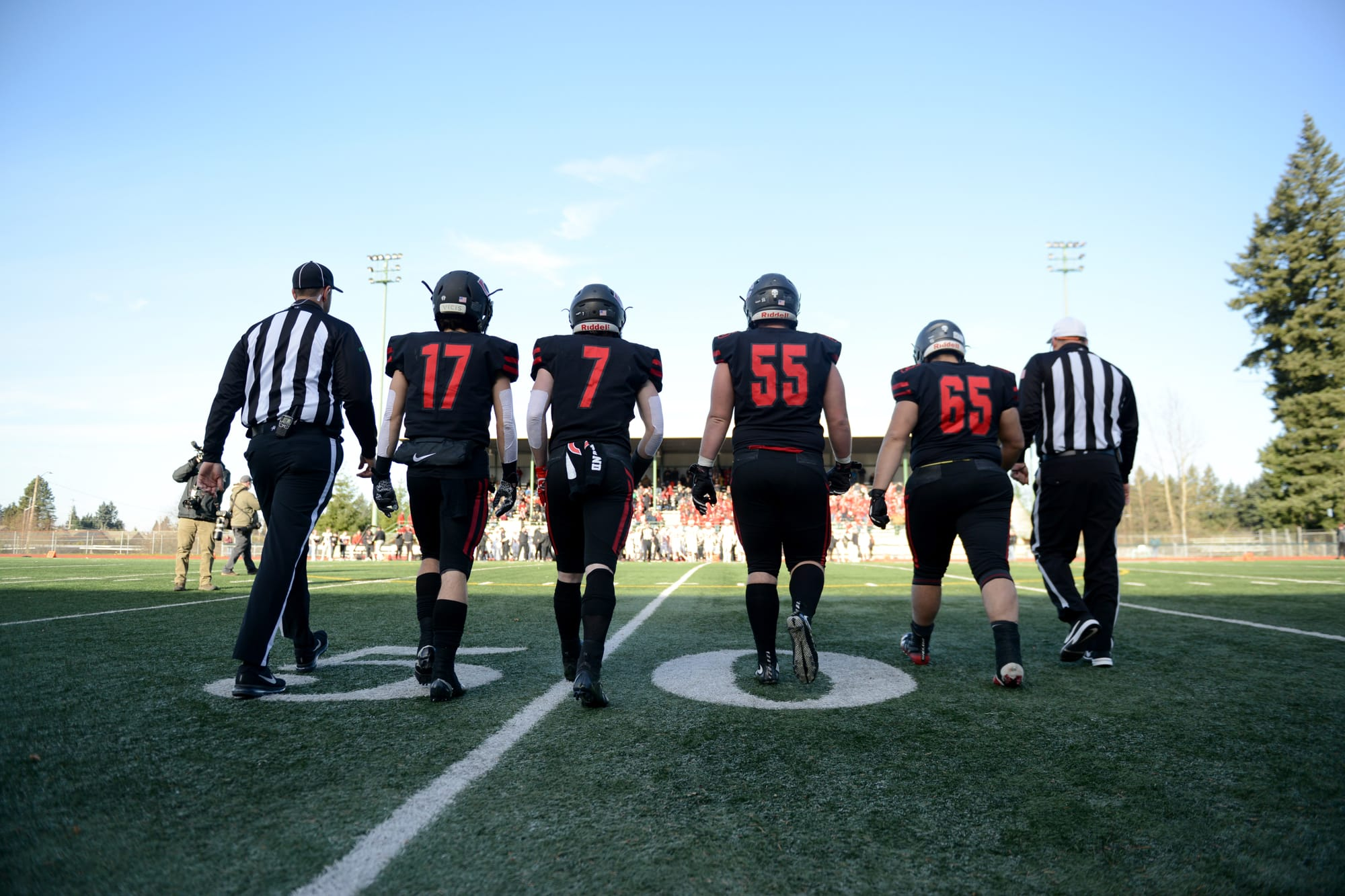 Camas football players Kolby Broadbent, left, Tyler Forner, Tristan Souza, and Tai Tumanuvao approach the coin toss before a game against Mount Si at McKenzie Stadium on Saturday afternoon, November 30, 2019. Camas beat Mount Si 35-14 to move on to the 4A state title game. (Samuel Wilson for the Columbian)