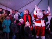 Mayor Anne McEnerny-Ogle, Santa and Princess Pearle (left, being held), 2, wave to a crowd of more than 5,000 people who came out to see the tree lighting Friday night in Esther Short Park. McEnerny-Ogle asked Pearle to help her officially light the tree this year.