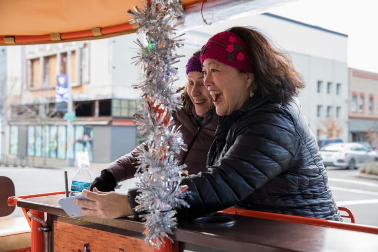 Michele Thayer, left, and Jeannie Jacobs laugh while taking a selfie on the Couve Cycle party bike Saturday afternoon in downtown Vancouver. (Elayna Yussen for The Columbian)