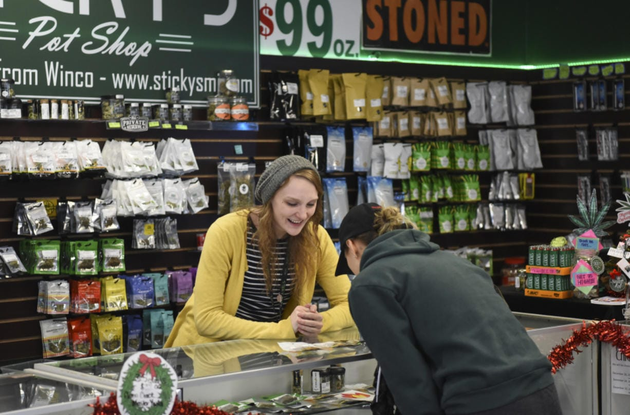Sarah Rosdahl, budtender at Sticky's Pot Shop in Hazel Dell, helps a customer in 2017. The store was forced to close last year following a lengthy legal battle with Clark County. The Clark County council has since voted to lift a moratorium on marijuana businesses in unincorporated areas. (The Columbian files)