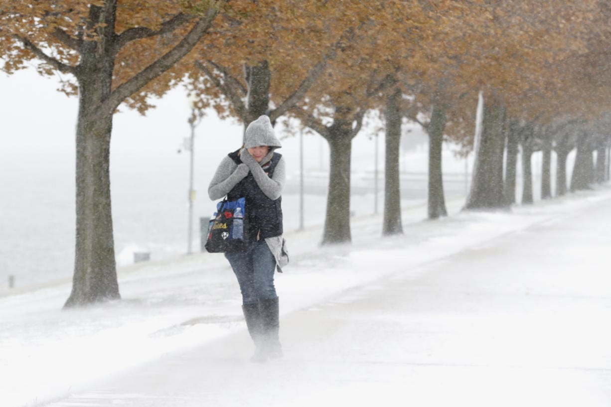 A woman is buffeted by the stiff wind and blowing snow off Lake Michigan as she walks Monday in Chicago.