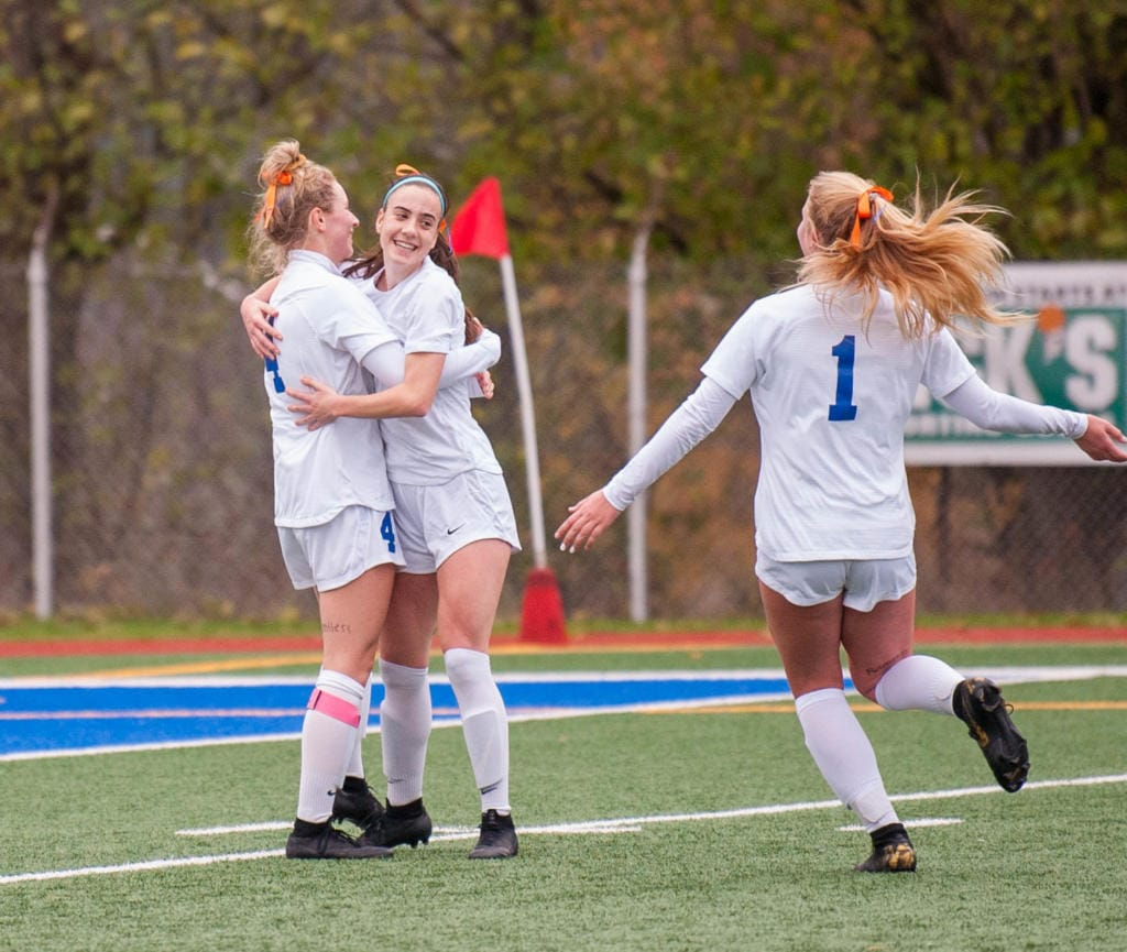 Brooke Weese, Taylor Hope and Elizabeth Farley celebrate Weese's second goal in Ridgefield's win over Selah in the 2A third-place game Saturday at Shoreline Stadium.