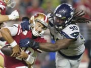 Seattle Seahawks defensive end Jadeveon Clowney (90) tries to take down San Francisco 49ers quarterback Jimmy Garoppolo during the the game on, Monday, Nov. 11, 2019.