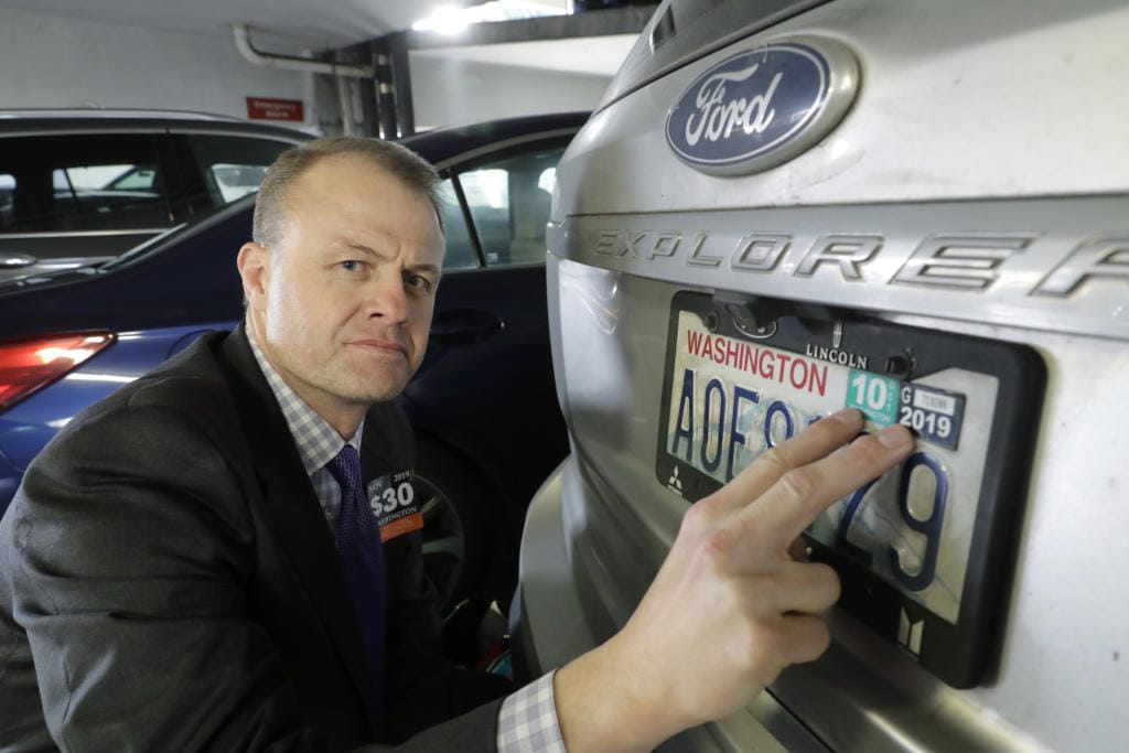 Tim Eyman, a career anti-tax initiative promoter, poses for a photo with the expired car registration tabs on his SUV, Tuesday, Nov. 26, 2019, in a parking garage in Seattle.(AP Photo/Ted S. Warren)