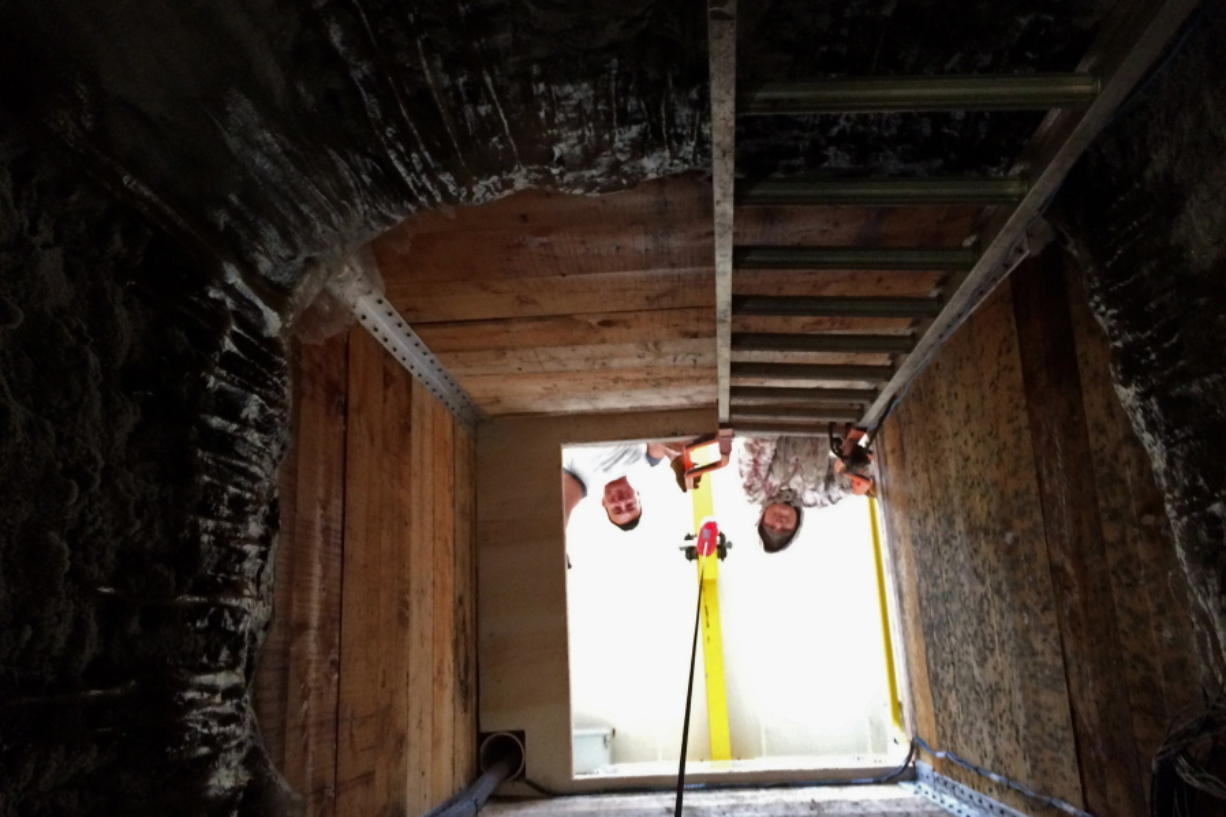 In this undated photo, two men look down a shaft in Kaktovik, Alaska, leading to a new community ice cellar, a type of underground food cache dug into the permafrost to provide natural refrigeration used for generations in far-north communities. (Marnie Isaacs/Kaktovik Community Foundation)