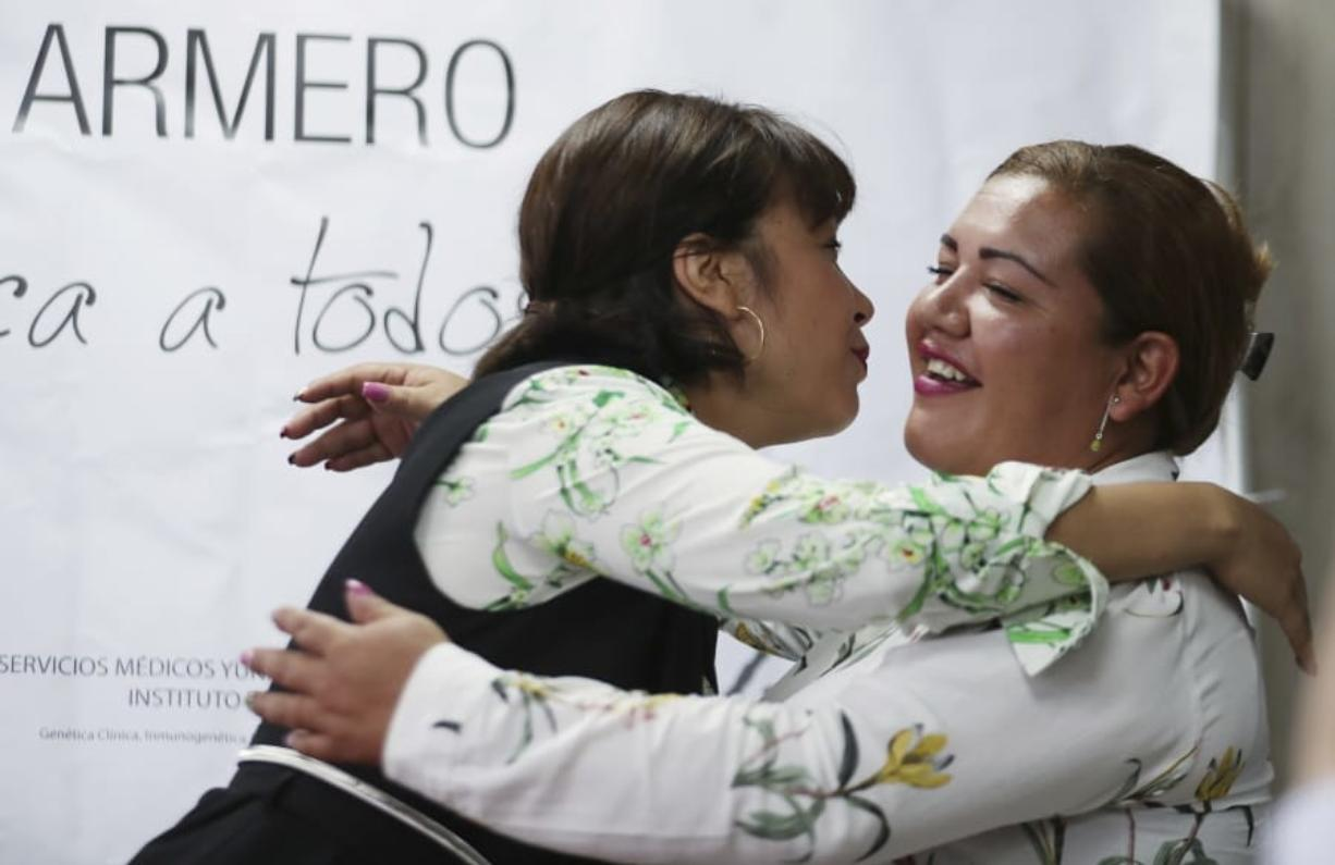 Jenifer De La Rosa, left, embraces her sister Angela Rendon after a press conference in Bogota, Colombia, Thursday, Nov. 14, 2019. The story of the sisters could be one of many involving children who were separated from their parents after the Nevado del Ruiz erupted, rescued from the rubble and later put up for adoption after no relative arrived to claim them. A genetic institute in Colombia's capital confirmed through DNA testing that Jenifer De La Rosa and Angela Rendon are sisters. (AP Photo/Fernando Vergara)