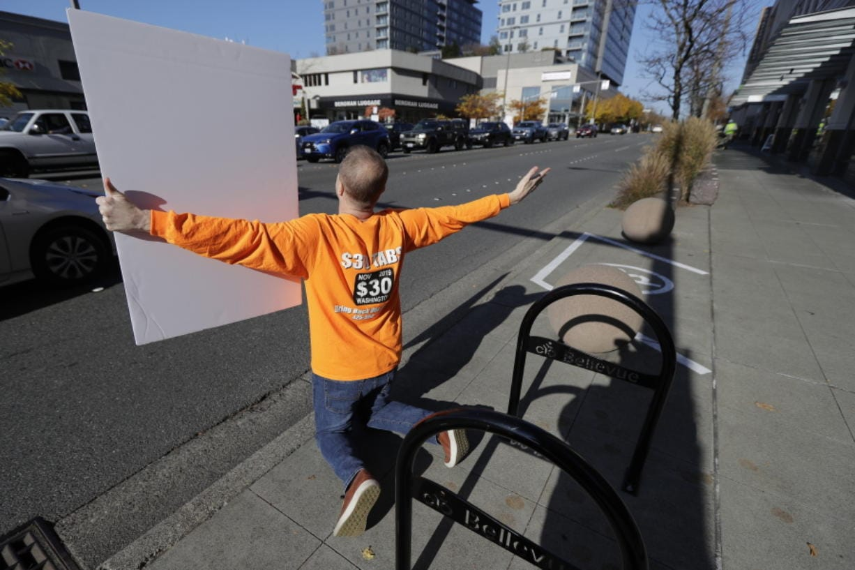 Anti-tax activist Tim Eyman kneels and begs motorists to honk their horns as he holds a sign supporting Initiative 976, which would cut most car tabs to $30 in Washington state, Tuesday, Nov. 5, 2019, on election day in Bellevue, Wash. If passed by voters, the measure would leave state and local governments scrambling to pay for road paving and other transportation projects. (AP Photo/Ted S. Warren)