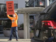 Anti-tax activist Tim Eyman holds a sign supporting Initiative 976, which would cut most car registration tabs to $30 in Washington state, Tuesday, Nov. 5, 2019, on election day in Bellevue, Wash. If passed by voters, the measure would leave state and local governments scrambling to pay for road paving and other transportation projects. (AP Photo/Ted S.