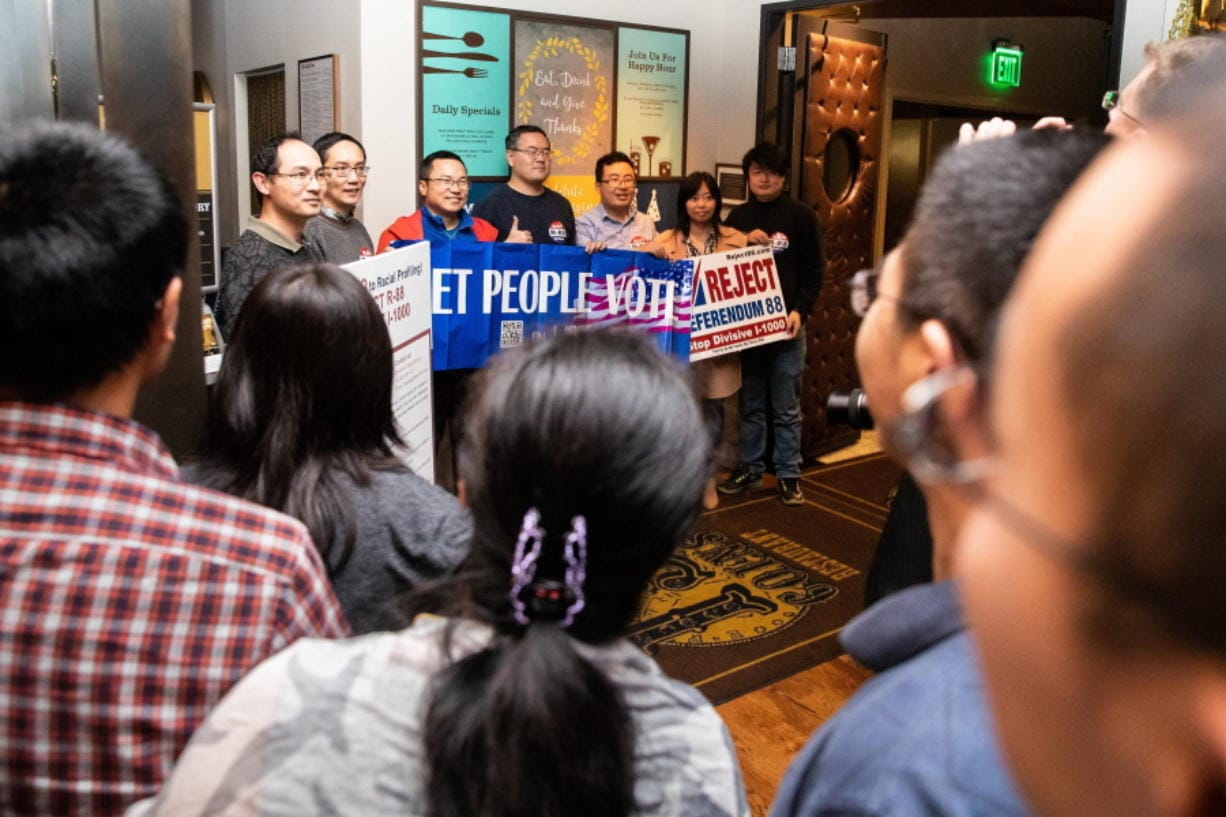 Supporters take photos with their banners and signs as polls show an early lead for the anti-affirmative action group Reject Referendum 88 at their election-watching event at 13 Coins in Bellevue on Tuesday, Nov. 5, 2019.