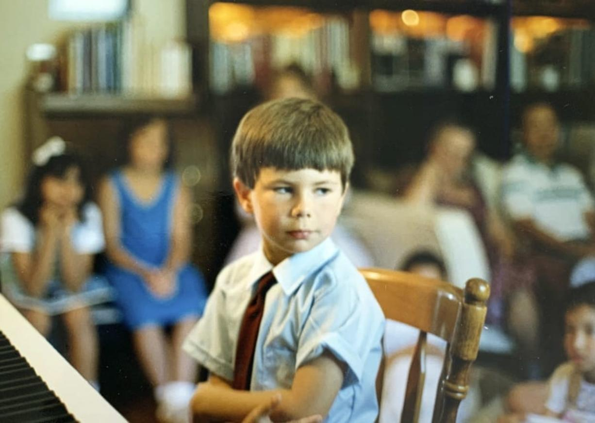 In this image provided by the Pete Buttigieg presidential campaign, Pete Buttigieg sits at a piano in a a Montessori graduation event for parents in South Bend, Ind., around 1987.