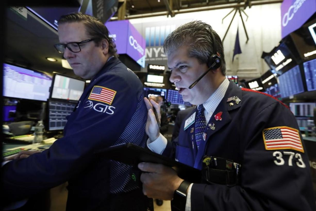 FILE - In this Tuesday, Oct. 29, 2019, file photo specialist Gregg Maloney, left, and trader John Panin work on the floor of the New York Stock Exchange. The U.S. stock market opens at 9:30 a.m. EDT on Friday, Nov. 1.