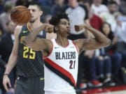 Portland Trail Blazers center Hassan Whiteside, right, flexes after making a basket over Atlanta Hawks center Alex Len during the first half of an NBA basketball game in Portland, Ore., Sunday, Nov. 10, 2019.