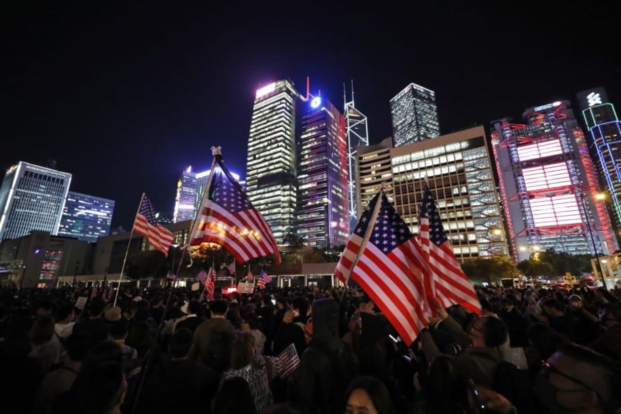 """Protester holds U.S. flags during a demonstration in Hong Kong, Thursday, Nov. 28, 2019. China's fury over President Donald Trump's decision to sign legislation supporting human rights in Hong Kong is evident. What's less clear what """"countermeasures"""" Beijing may take in response to what it said Thursday were """"extremely evil"""" and dangerous moves."""