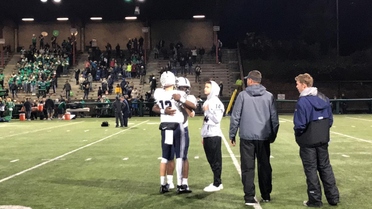 Skyview's Yaro Duvalko (12) and Jalynnee McGee embrace after Saturday's 38-17 loss to Woodinville in the teams' 4A first-round state playoff game in Bothell.
