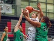 Union's Mason Oberg drives between a pair of Kentwood defenders in a girls basketball game at Union High School.