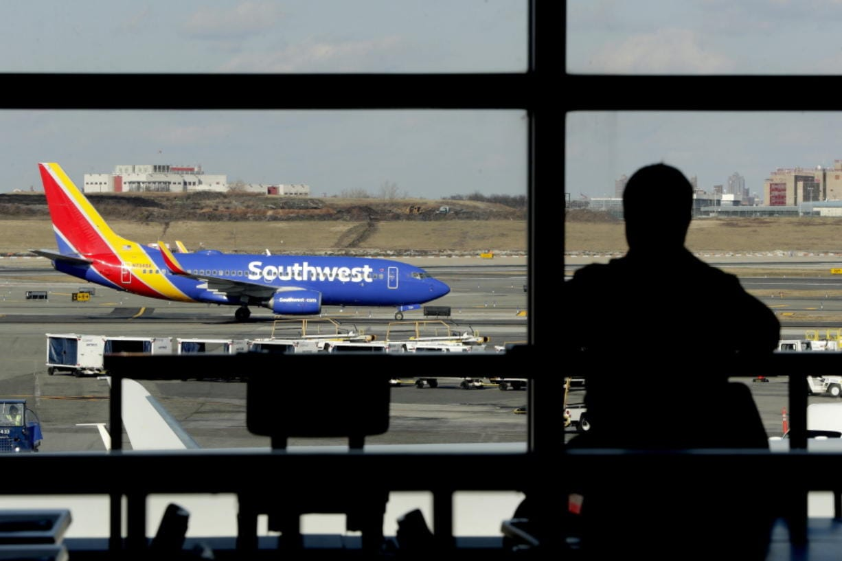 FILE- In this Jan. 25, 2019, file photo a Southwest Airlines jet moves on the runway as a person eats at a terminal restaurant at LaGuardia Airport in New York. The National Transportation Safety Board is meeting Tuesday, Nov. 19  in Washington to consider the cause of a deadly engine failure on a Southwest Airlines flight last year. The incident killed a passenger who was blown partly out of the plane when a piece of the engine shattered the window next to her.