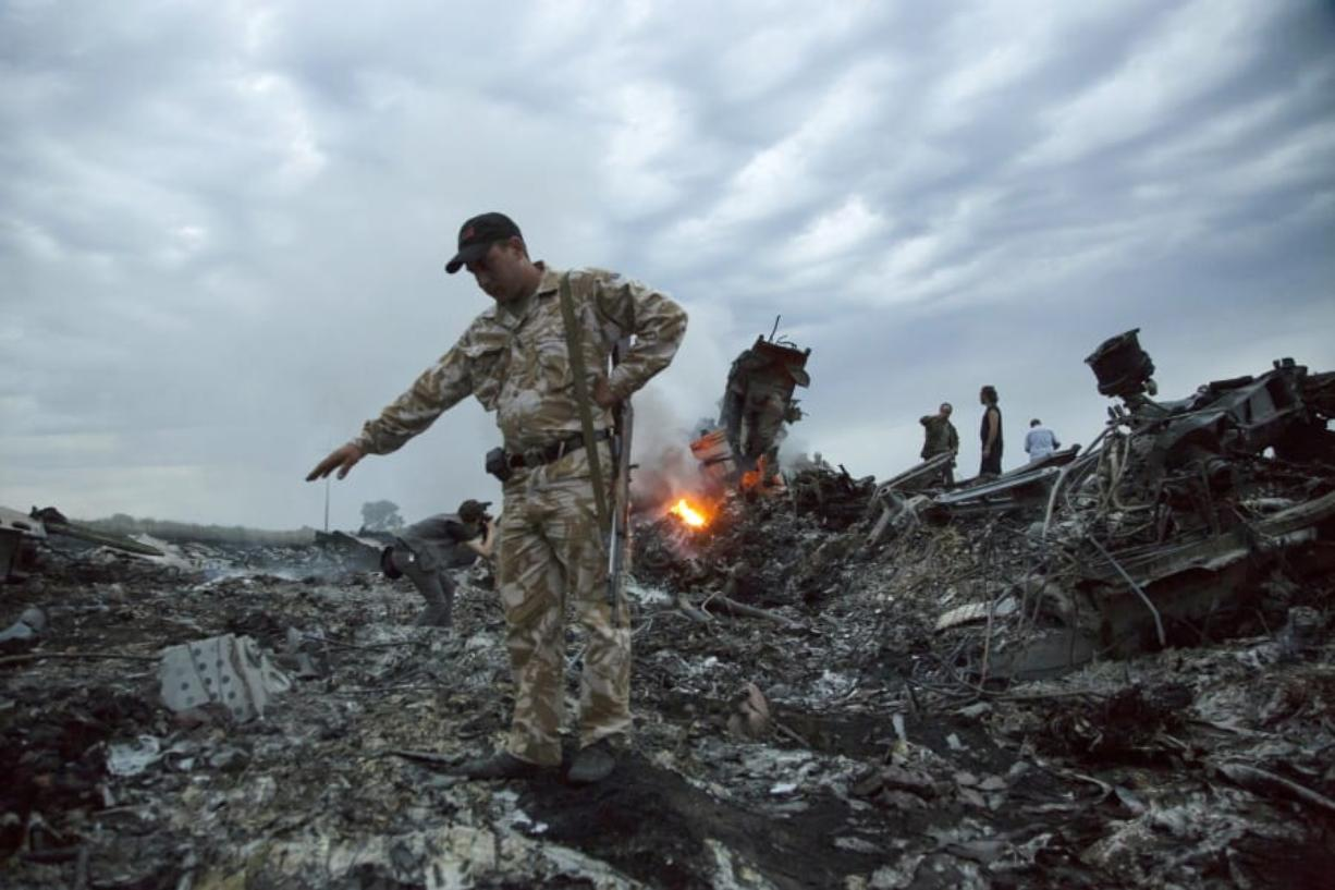 FILE - In this July 17, 2014. file photo, people walk amongst the debris at the crash site of MH17 passenger plane near the village of Grabovo, Ukraine, that left 298 people killed. An international team of investigators piecing together a criminal case in the July 2014 shooting down Malaysia Airlines Flight 17 over eastern Ukraine said Thursday Nov.