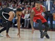 Portland Trail Blazers guard Damian Lillard, right, dribbles around Brooklyn Nets guard Garrett Temple during the first half of an NBA basketball game in Portland, Ore., Friday, Nov. 8, 2019.