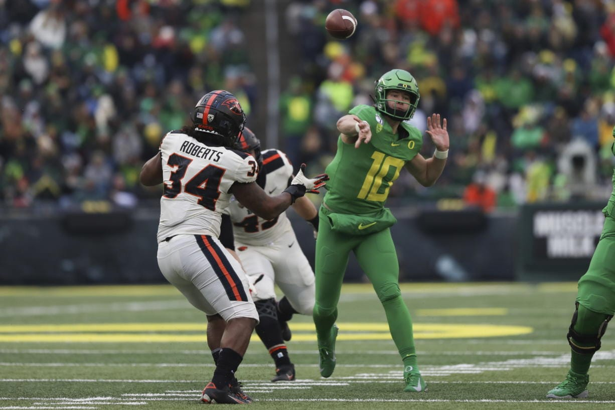 Oregon quarterback Justin Herbert (10) throws a pass away from Oregon State inside linebacker Avery Roberts (34) and defensive lineman Simon Sandberg (45) during the second half of an NCAA college football game in Eugene, Ore., Saturday, Nov. 30, 2019.