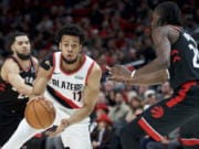 Portland Trail Blazers forward Skal Labissiere, center, dribbles around Toronto Raptors forward Chris Boucher, right, during the first half of an NBA basketball game in Portland, Ore., Wednesday, Nov. 13, 2019.