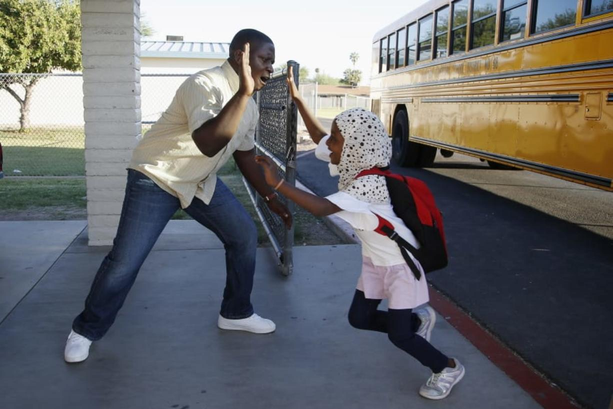 Samuel Lavi, left, a Congolese native who is a teaching assistant and family engagement liaison, greets first-grader Kediga Ahmed as she arrives Oct. 17 at Valencia Newcomer School in Phoenix. (Ross D. Franklin/Associated Press)