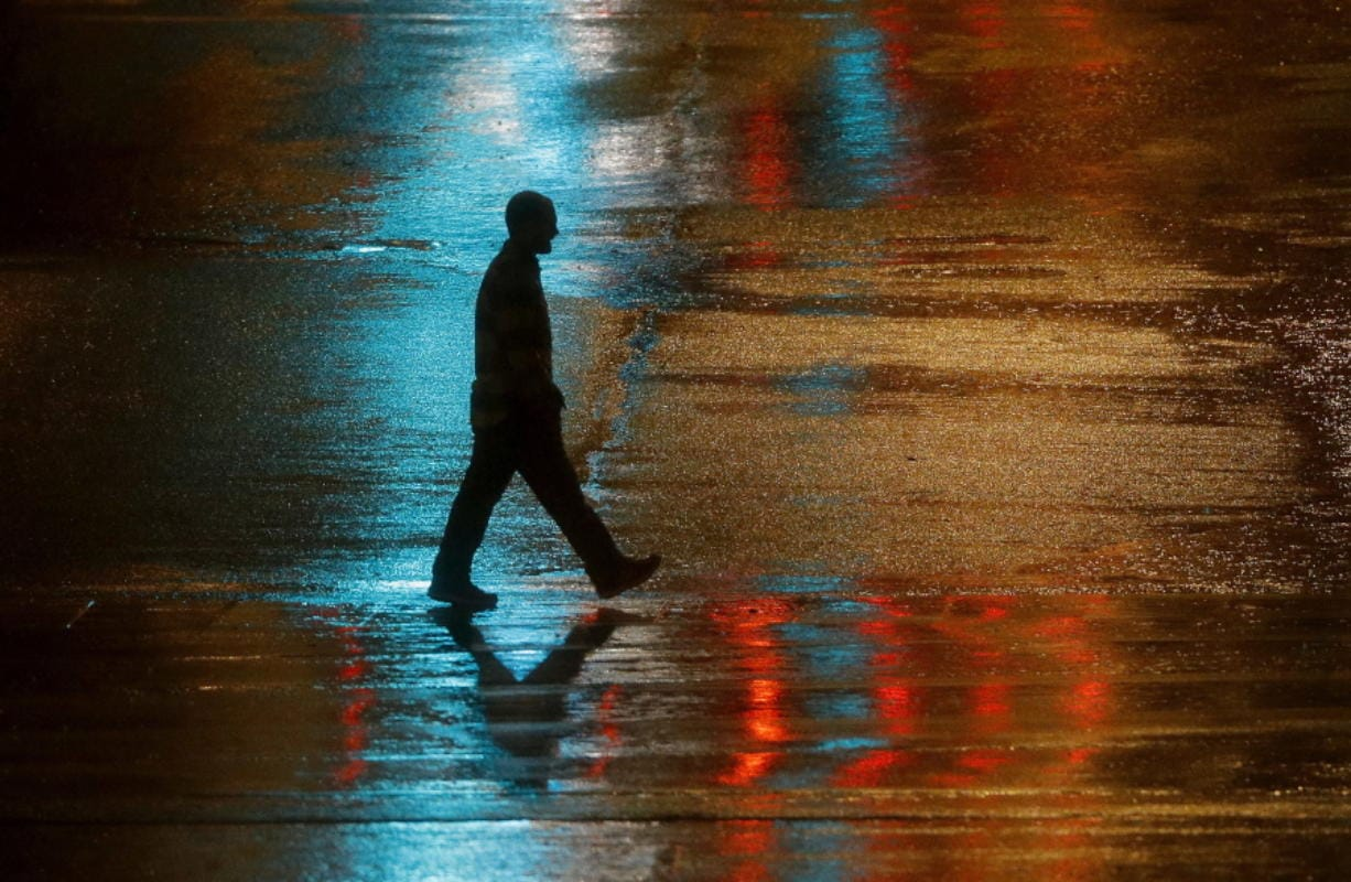 FILE - In this Wednesday, Dec. 26, 2018 file photo, a pedestrian is silhouetted against wet pavement in Kansas City, Mo. In a first-of-its-kind report released Tuesday, Nov. 5, 2019, the Centers for Disease Control and Prevention estimates that millions of cases of heart disease and other illnesses can be linked to abuse and other physical and psychological harm that patients suffered as children. (AP Photo/Charlie Riedel)