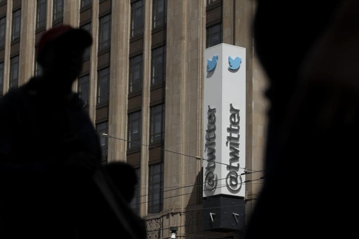 FILE - This July 9, 2019, file photo shows pedestrians walking across the street from the Twitter office building in San Francisco. The Saudi government recruited two Twitter employees to get personal account information of their critics, prosecutors said Wednesday, Nov. 6, 2019.
