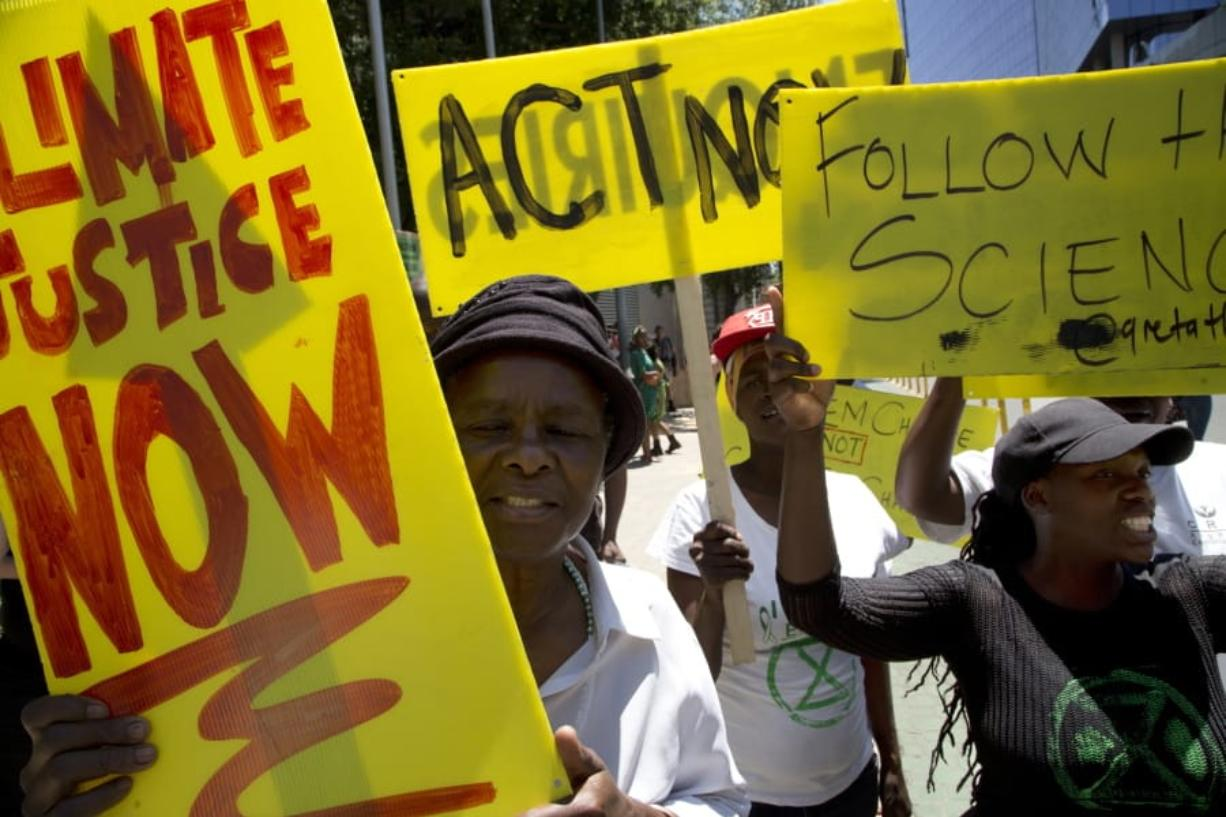 Demonstrator show their placards during climate change protest outside the Johannesburg Stock Exchange in Johannesburg, South Africa, Friday, Nov. 29, 2019.  Environmentalists around the world are joining a global day of protests Friday, in a symbolic gesture to demand that governments act against climate change. (AP Photo/Denis Farrell) (jens meyer/Associated Press)
